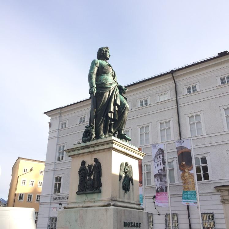 Estatua de Mozart na Mozartplatz. Ao fundo o Museu de Salzburg e o Neue Rezidenz